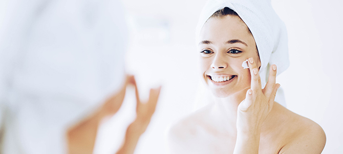 A young girl looks in the mirror as she applies a skin cleanser to her face